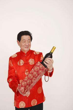 Senior man holding a bottle of wine photo