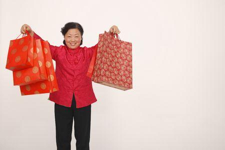 Senior woman holding up shopping bags photo