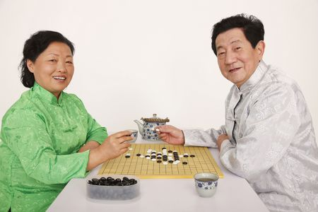 Senior man and woman playing japanese board game photo