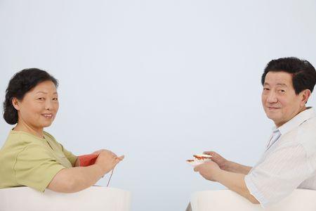 Senior woman knitting while senior man is enjoying a cup of tea photo