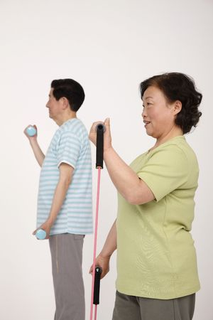 Senior man lifting weight while senior woman is exercising with elastic band photo