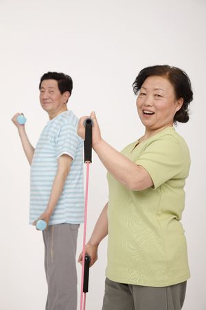 Senior man lifting weight while senior woman is exercising with elastic band