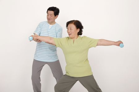 Senior man guiding senior woman in lifting weights