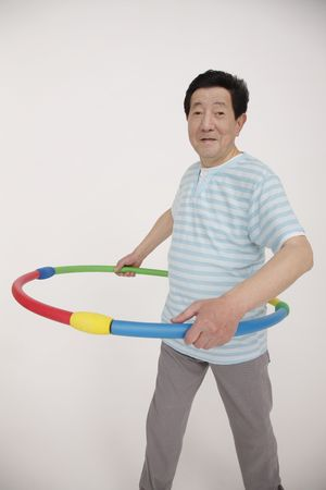 Senior man using hula hoop