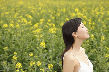 adult rape: Woman standing at the field with her eyes closed Stock Photo