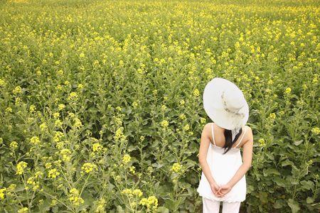 adult rape: Woman with hat enjoying the view of rape field
