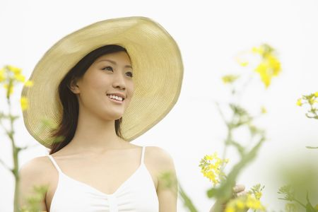 Woman with hat smiling while looking away photo