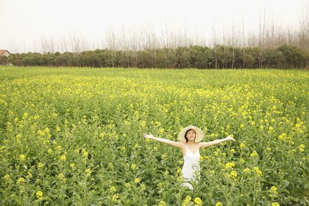 adult rape: Woman standing at the rape field with her arms outstretched