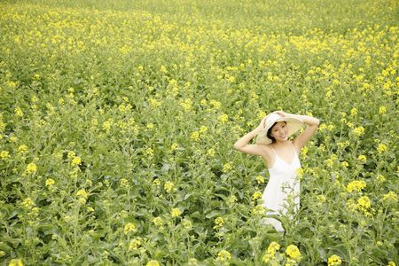 Woman standing at the rape field, smiling photo