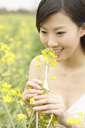 Woman smelling oilseed rape photo