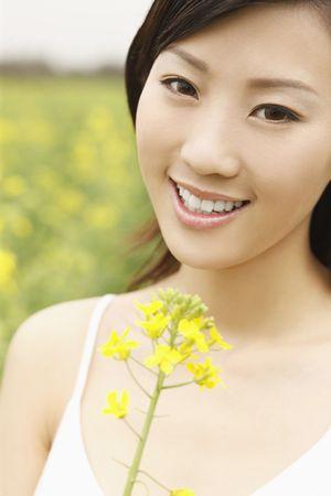 Woman holding oilseed rape, smiling photo