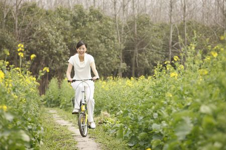 Woman cycling on alley between rape fields Stock Photo