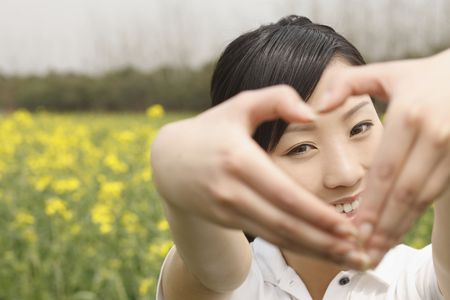 Woman forming a heart shape with her fingers photo