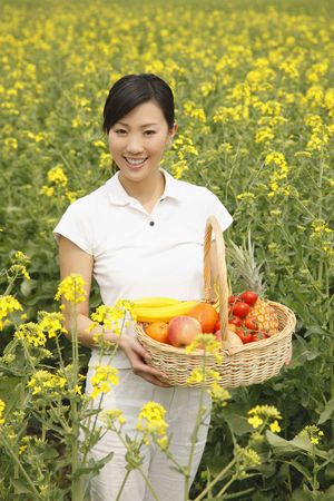 Woman holding a basket of fruits photo