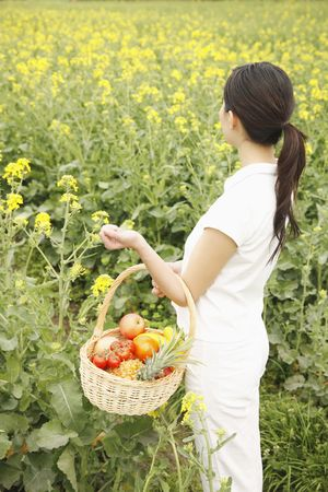 Woman carrying a basket of fruits photo