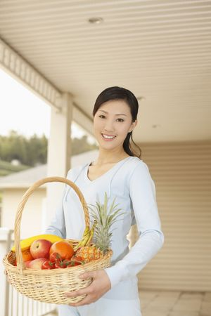 Woman holding a basket of fruits, smiling photo