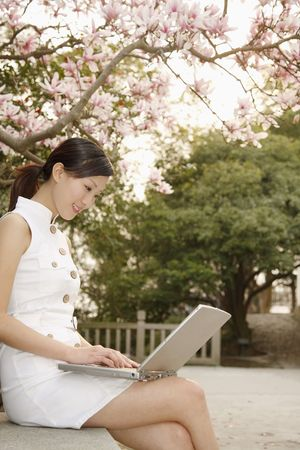 Woman sitting on the bench using laptop photo