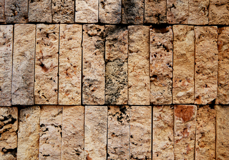 Natural beige stone wall background decorative masonry from brick tiles