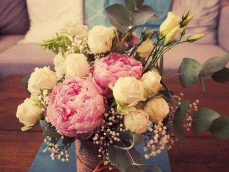 Bouquet decoration on the table in living room. Vintage style photo. Nosegay with pink peony, white roses, lisianthus, gypsophila and eucalyptus leaves