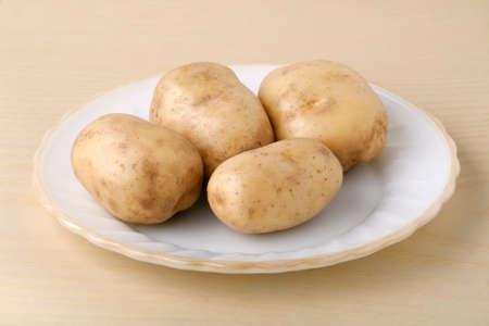 Fresh potatoes on a white plate
