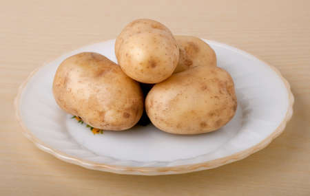 Fresh potatoes on a white plate