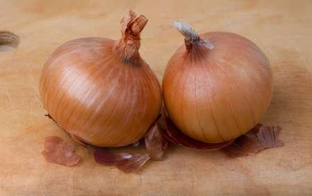 Fresh onions on wooden board