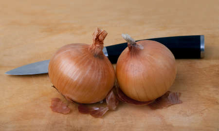 Fresh onions and knife on wooden board Stock Photo