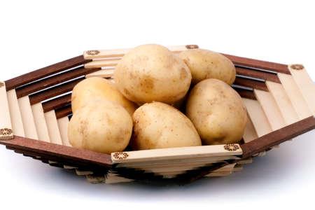 Fresh potatoes in wooden vase isolated Stock Photo
