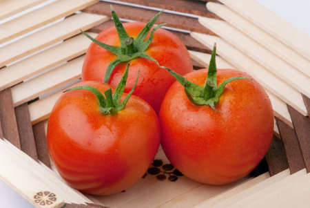 red tomatoes in wooden vase