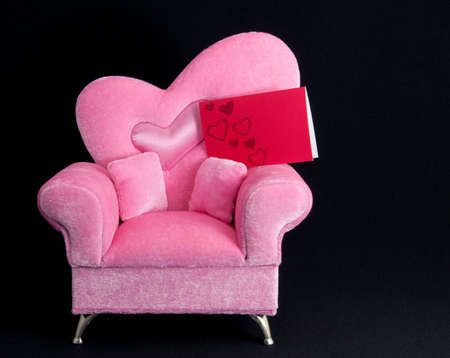 Black back ground and pink chair.