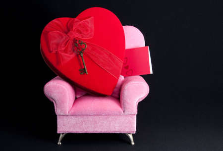 Heart and key on arm chair with black background.