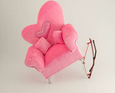 Red glass holding up a pink arm chair with a heart in the center. Stock Photo