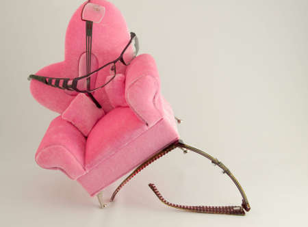 Eye glass holding up pink arm chair with with a white back ground.