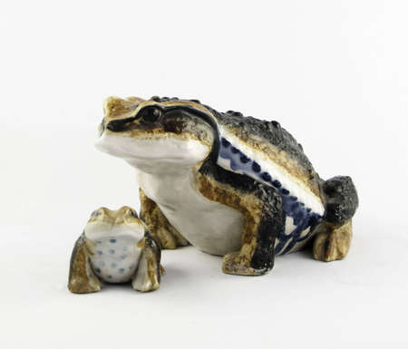 Porcelain frogs on a white background.