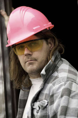 A worker wearing a pink hardhat and yellow safety glasses. Imagens