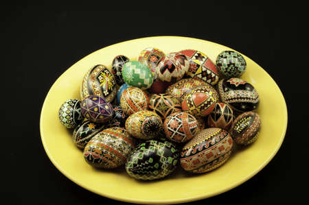 A plate of pysanky eggs on a plate with black background.5