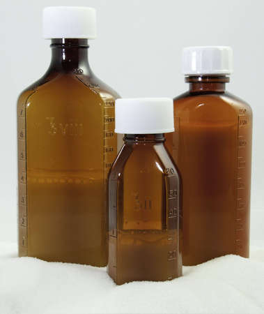 Three medicine bottles partially filled on sugar base with white background.