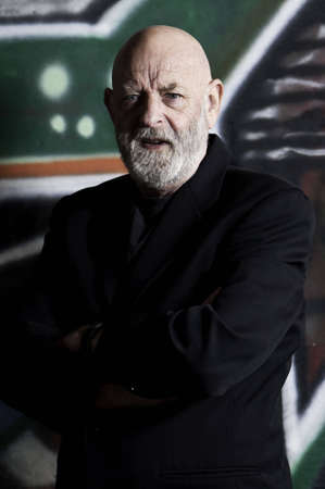 he: Man has his arms folded and is wearing a black sport jacket. He also has a beard. Stock Photo