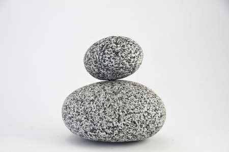 Two round granite rocks of different size. They are on a white background. Stock Photo
