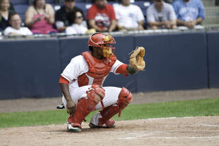 Baseball catcher showing the pitcher where to trhow the ball.