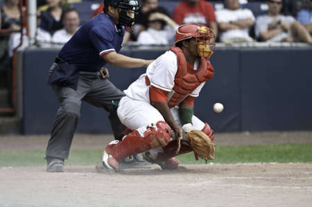 The catcher standing up quickly you can see the dirt being kick up by his cleets. The ball is in the air. Stock Photo