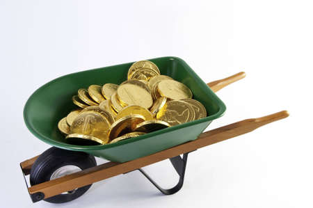 Top view of gold coins filling  a green wheel barrel.It is on a white background. Stock Photo
