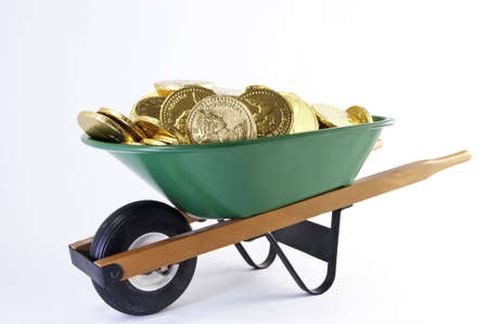 bucket of money: Side view of gold cooins filling a green wheel barrel.It is ona white background.