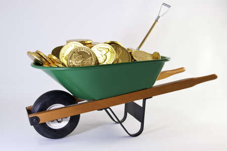 Green wheel barrel full of gold coins and shovel also inside.It is on a white background.