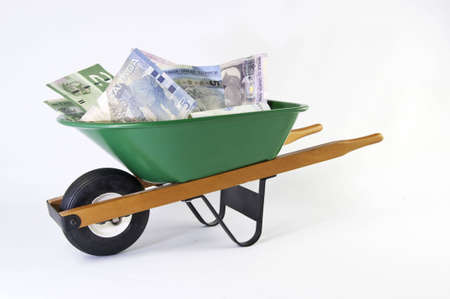 wheel barrel: Wheel barrel full of dollars on a white background.