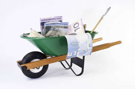 Green wheel barrel with shovel  and canadian currency and coins. It is on a white background.