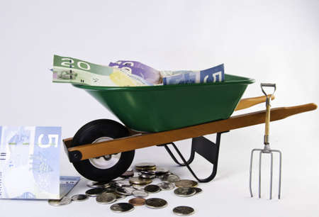 Green wheel barrel with shovel and pitch fork and canadian currency and coins. It is on a white background.