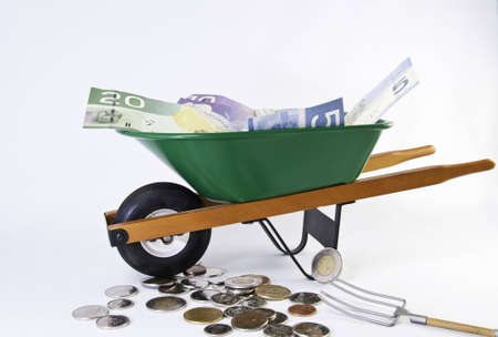 wheel barrel: Canadian  dollars filling a green wheel barrel with more money under it. View from side.White background. Stock Photo