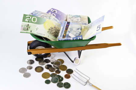 wheel barrel: Canadian dollars filling a green wheel barrel with more money under it. View from top.White background.