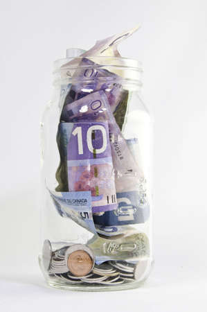 canadian currency: Canadian dollars in jar with coins. Stock Photo